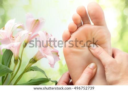 Macro cận cảnh massage chân bên cạnh hoa đầy màu sắc và nền màu xanh lá cây.