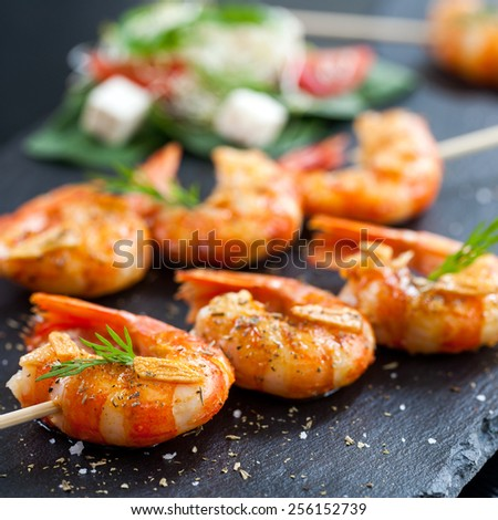Macro close up of giant aromatic prawn tails spiced with natural herbs and grilled on wood skewer. - stock photo