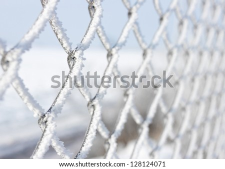Macro close-up of metal fence covered with frozen snow