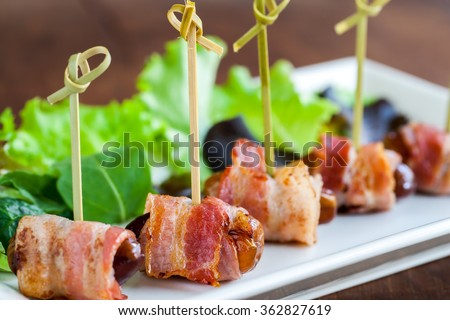 Macro close up of multiple date and bacon appetizers mounted on small skewers. - stock photo