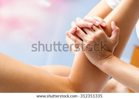 Macro close up of osteopath massaging female calf muscle. Hands manipulating lower leg muscle. - stock photo