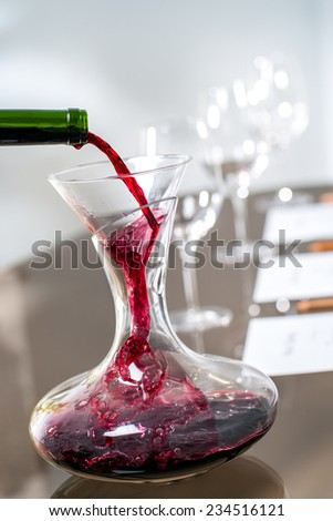 Macro close up of Red wine pouring into decanter at wine tasting. - stock photo