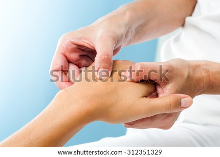 Macro close up of Therapist doing massage on female hand.Osteopath applying pressure on hand. - stock photo