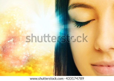 Macro close up of young woman meditating with eyes closed.Conceptual spiritual background with light beam. - stock photo