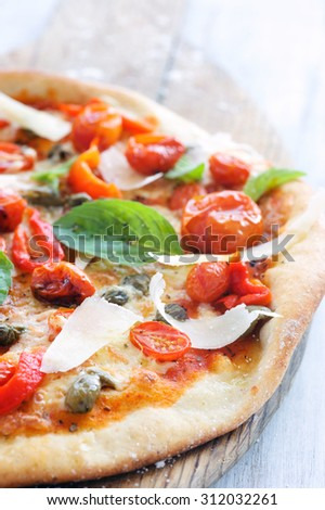 Macro close up on rustic pizza with oven roasted tomatoes, peppers, capers, basil and shaved cheese  - stock photo
