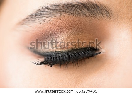 Macro closeup of a closed woman's eye with fake eyelashes and some makeup on