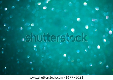 Macro closeup of abstract teal glitter texture. Shimmering blur background with shining lights. Vibrant color. - stock photo