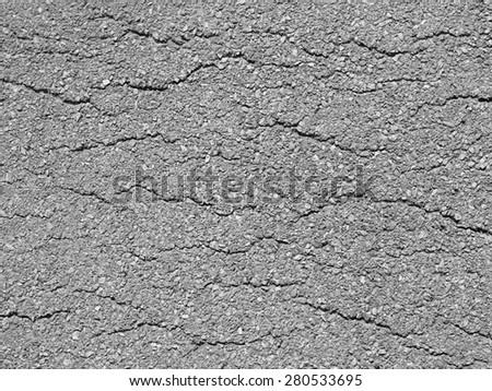 Macro closeup on concrete asphalt cracks on the road texture - stock photo