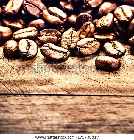 Macro Coffee beans on grunge wooden background. Fresh Roasted coffee beans on vintage table. - stock photo