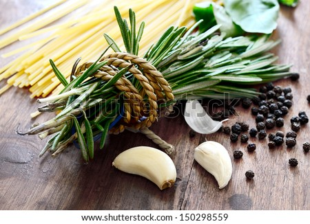 Macro composition of Italian cooking ingredients, garlic, rosemary, basil leaves, spaghetti and black peppercorns on old kitchen table shot in natural light. - stock photo