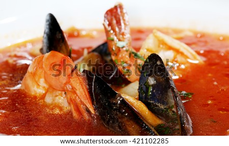 macro delicious red soup with mussels in a white plate on a dark background