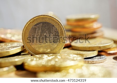 Macro detail of a pile of coins on the wooden surface with a silver and golden Euro coin separated from other metallic coin currencies
