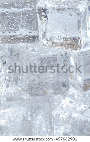 Macro detail of group of ice cubes with water droplets - vertical photo - stock photo