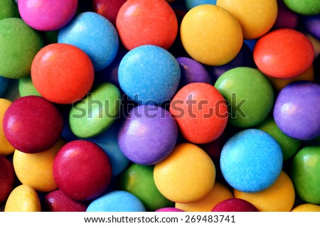 Macro detail of pile of colored smarties background. Close-up of candies texture. - stock photo