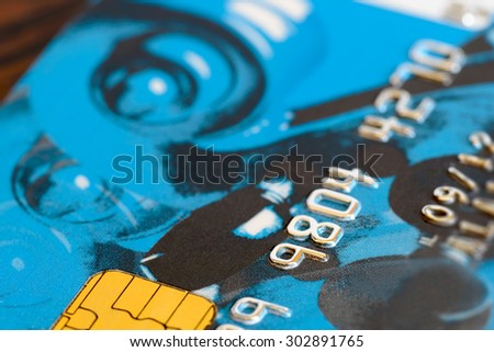Macro detail of the numbers on a plastic credit card with golden electronic chip