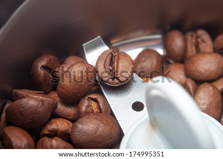 Macro electric coffee-mill machine with roasted coffee beans on isolate background