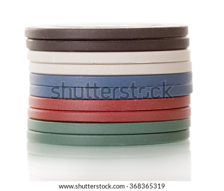 Macro. Green, red, blue, white, black poker chips in the form of a tower isolated