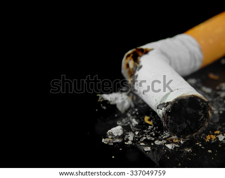 Macro image of a crushed cigarette butt on a black background is a quit smoking concept. Copy space for your message. Good for the Great American Smokeout Day in November or any lung cancer issue - stock photo