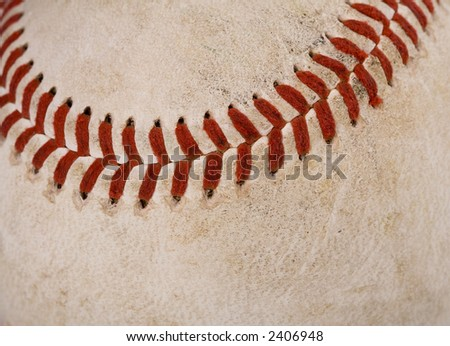 Macro image of a dirty baseball. Primary focus is on the stitching. - stock photo