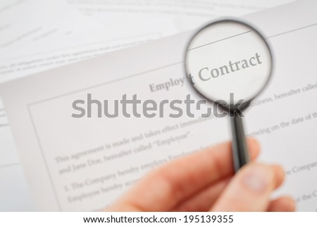 Macro image of a hand holding a small magnifying glass and reading a contract. - stock photo