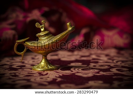Macro image of a tiny, gold antique Aladdin lamp ornament close-up.
