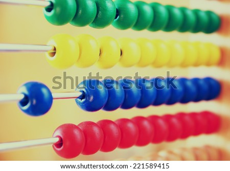 macro image of Beaded Abacus over wooden textured background. retro filtered image. selective focus  - stock photo