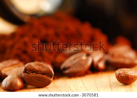 Macro image of coffee beans and ground coffee with black coffee cup