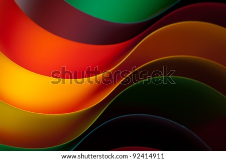 macro image of colorful curved sheets of paper shaped like a fan, on orange background - stock photo