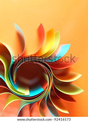 macro image of colorful curved sheets of paper shaped like a flower, on orange background