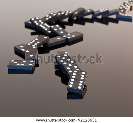 Macro image of dominos on a black reflactive surface and collapsed in pile - stock photo