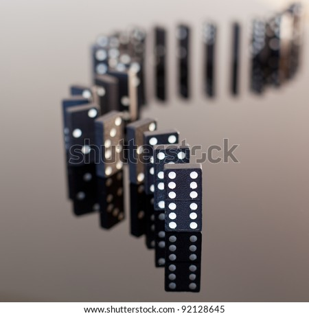 Macro image of dominos on a black reflactive surface and standing in a row - stock photo