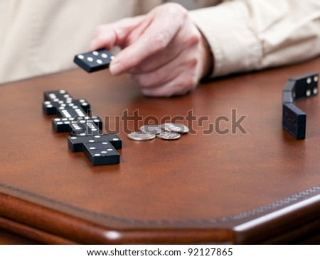 Macro image of dominos on a leather table in the middle of a game with hand placing a tile - stock photo