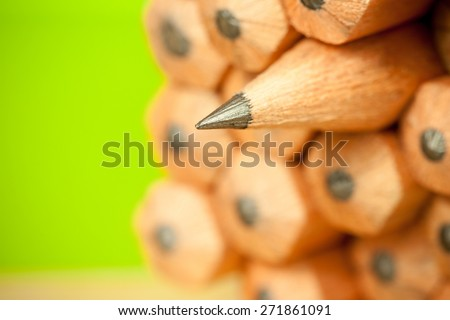 Macro image of graphite tip of a sharp ordinary wooden pencil as drawing and drafting tool, standing among other pencils, symbolizing individuality approach and concept as standing out from the crowd - stock photo