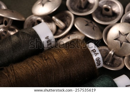 macro metal buttons with a star and spools of thread on a dark background studio - stock photo