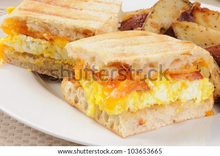Macro of a bacon, egg and cheese breakfast panini with fried potato ...