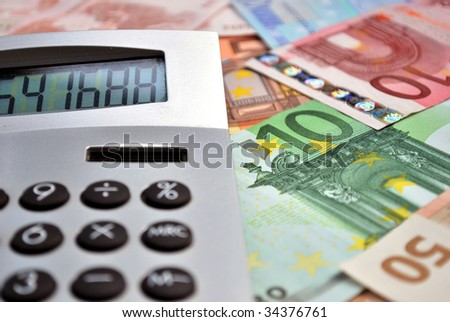 macro of a calculator over many euro banknotes