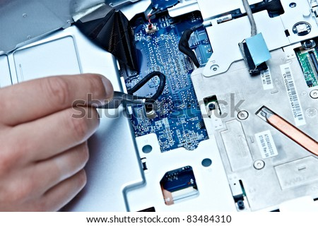 macro of a hand holding tweezers on a laptop connector - stock photo