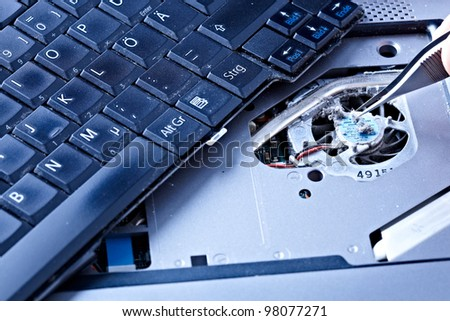 macro of a hand holding tweezers on a laptop fan - stock photo