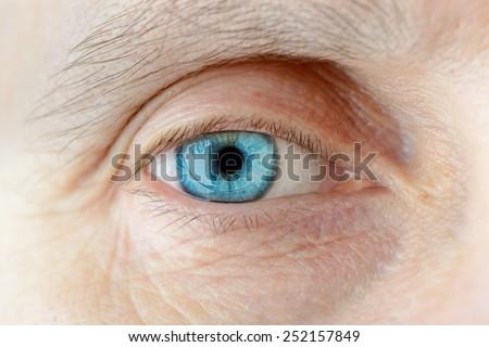 Macro of a hard contact lens on woman's blue eye - stock photo