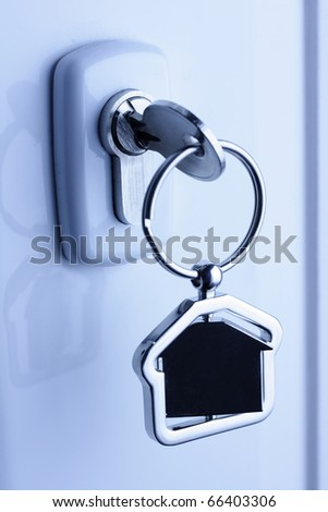 Macro of a lock and key with metal house figure - stock photo