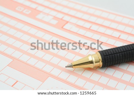 macro of a pen lying on a blank form full of empty boxes - stock photo