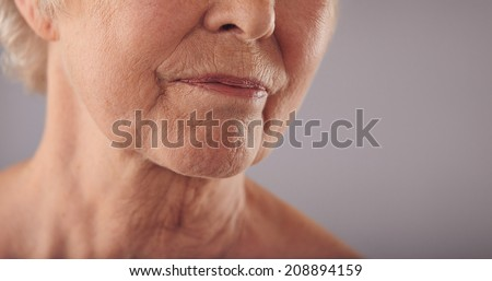 Macro of a senior female face with wrinkled skin against grey background. Cropped old woman face. - stock photo