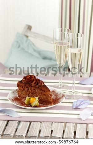 macro of a table with two glass of champagne and a piece of cake