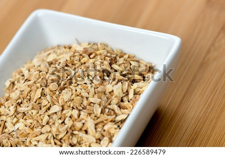 Macro of astragalus root chips against a wooden board - stock photo
