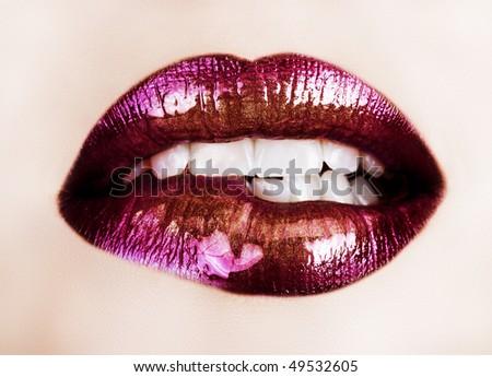 macro of beautiful lips with purple and gold lipstick - stock photo