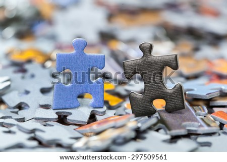 Macro of black and blue puzzle pieces on a pile of jigsaw pieces. Shallow depth of field - stock photo