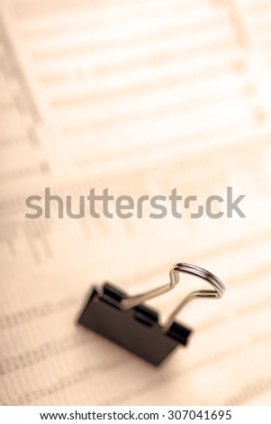Macro of black paperclip against financial newspaper, warm filter. - stock photo