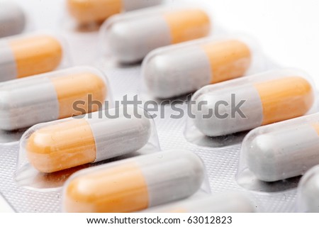 Macro of blister pack of white-orange pills isolated on white background angle view. Tablets or Pills flu treatment therapy packaging antibiotic pharmacy medicine medical image. Pills in blister pack - stock photo