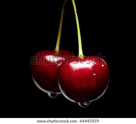 Macro of cherry bunch isolated over black background - stock photo