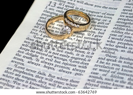 Macro of 1 Corinthians 13:4 Love is Patient with Wedding Bands - stock photo
